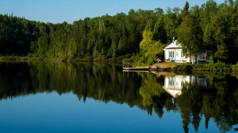 Rural home / cottage  on a lake in the morning in Canada. The lake is quiet and the house reflected in the lake.