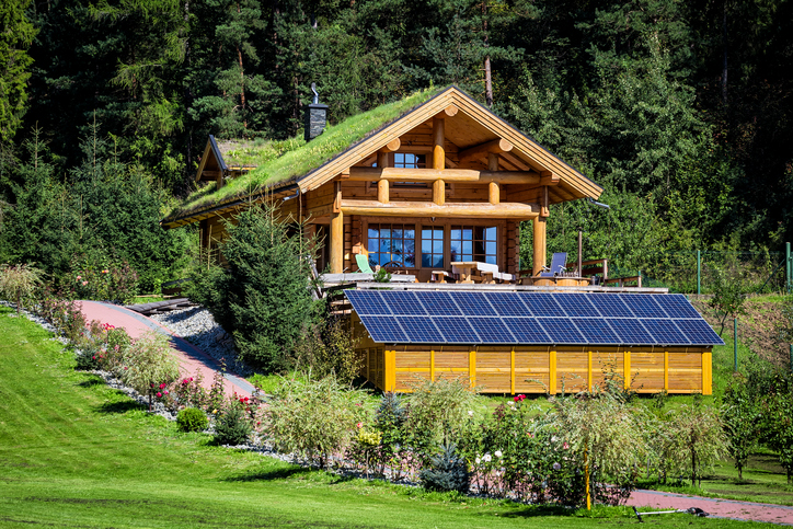 Summer view of wooden country style holiday villa / cottage with solar panels
